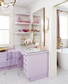 Chic dressing room features brass mirror flanked by Hudson Valley Lighting Essex Wall Sconces next to lavender floating shelves filled with knick knacks over lavender vanity topped with tempered glass topped with lucite trays and brass lantern paired with Ghost Chair atop calacatta and thassos herringbone tiled floor. To see the whole family, visit: https://www.hudsonvalleylighting.com/Products/Family/essex