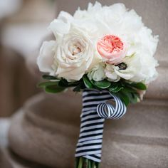 A combination of white roses, anemones, hydrangeas and peach garden roses was tied with black-and-white striped ribbon that tied in with the reception decor.