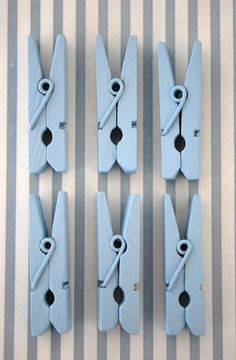 Light blue painted clothes pegs on stripey background / repetition We can put numbers on something like this for hanging up the baby pictures on the tree/wreath.