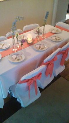 My sister-in-law just got engaged last Thursday.  She's pretty excited about getting married and having an elegant reception.  I think she'd love these white chair backers with the peach-colored bows.  It goes great with the runner going down the middle of this table.
