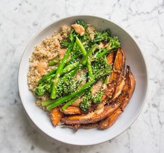 A vegan friendly salad bowl with roasted sweet potato wedges with broccoli, a peanut dressing, sesame seeds and quinoa. All gluten free, dairy free and vegetarian