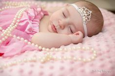 a beautiful little princess all pinked out and with her crown and pearls.