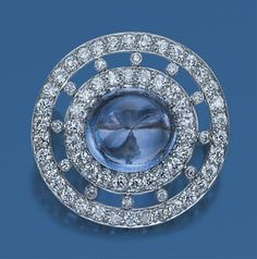 Diamond and Cabochon Sapphire Pendant-Brooch, Tiffany & Co.   Platinum, centering one oval cabochon sapphire approximately 14.20 cts., surrounded by 22 old European-cut diamonds, tipped by 10 small diamonds, further bordered by 34 old European-cut diamonds, altogether approximately 1.70 cts., signed Tiffany & Co., circa 1920