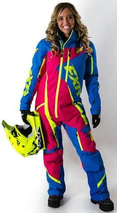 Remi is wearing an FXR deep pink,  indigo, & neon green snowmobile fullsuit.