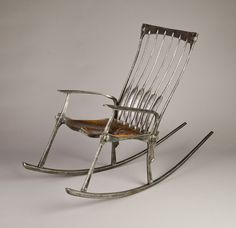Rocking chair -- wrought iron salvaged from old California gold country mine sites with a copper seat. Tim Cisneros and Brett Moten. A comfortable metal chair. A classic design reinterpreted in iron