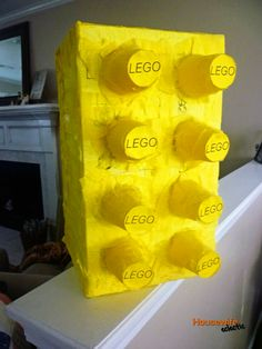 A Lego pinata made out of a box, tissue paper and yellow plastic cups.