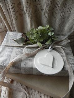 Love this gift wrapping style. #newspaper #gift #wrapping #packaging #ornament #white #heart #plaster #flowers #ribbon