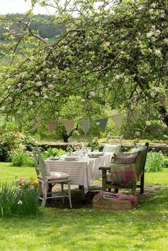 Country garden with a table and chairs, dappled in sunshine for out door countr6 eating.