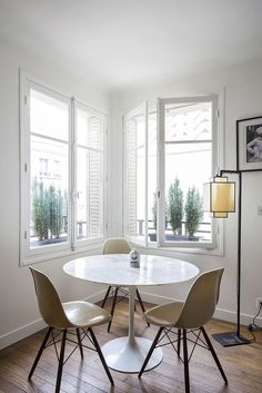 Eames Side Chairs with see-through bases that reference the Eiffel Tower keep the corner looking airy. So do the windows; Harden was able to forgo window treatments thanks to pocket shutters. The white on the walls is Farrow & Ball's Wimborne White.