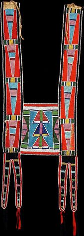 "Crow Martingale, ca. 1880 Horse collar of red and navy stroud, the long split tab suspensions with red and navy stroud tassels. The straps beaded in long triangles, and the center panel beaded with stacked triangles over a blue ground. 39"" long x 13"" wide. Peter Schramm Collection"