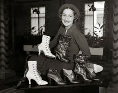 A model sitting behind a display of different boot styles, 1934. #vintage #1930s #boots #shoes
