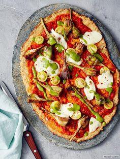 Die etwas andere Pizza besticht durch einen würzigen Gemüse-Parmesan-Boden. Darauf locken Artischocken, gelbe Tomaten, Mozzarella und, noch ein Clou, Erbsen-Basilikum-Pesto.