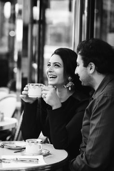 Beautiful indian woman laughing while drinking coffee in a typical Parisian cafés.  Wedding anniversary picture taken by The Paris photographer Fran Boloni