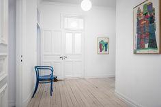 Bright art pieces brighten a white clean slate hal…