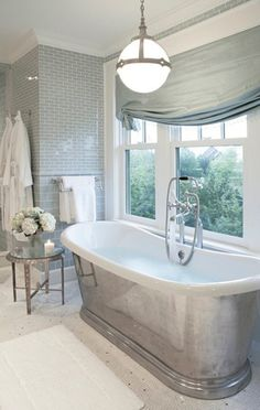 Large glass subway tiles below the chair rail with smaller ones above reflect light so nicely, and what a soothing color palette!  Silk soft roman shade adds luxury.  I mean, with a Waterworks tub <3 and a pendant from Urban Archaeology...this is really a decadent retreat!