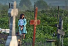 Stunning Photos Of Christians Observing Holy Week Around The World - A girl holds a plastic bag with food in a cemetery in the village of Copaciu, southern Romania, early Thursday, May 2, 2013. As part of a Holy Week tradition Romanians visit, on Maundy Thursday, the graves of their loved ones, light fires and share food with community members in memory of the departed. Orthodox worshipers celebrate Easter on May 5.(AP Photo/Andreea Alexandru, Mediafax) ROMANIA OUT