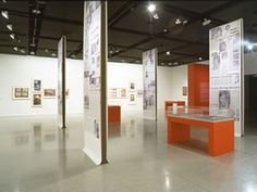 View of exhibition showing panels of newspaper collages, documents in display cases and poster art.
