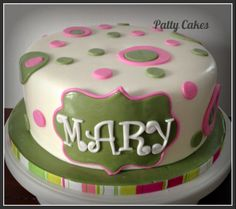 A simple fondant cake with pink and green circles.