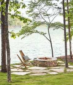Large flagstone pieces in grass joints with a stacked stone fire pit. Backyard Patio by the Lake - A pair of iconic clean-lined Kentucky stick chairs adds a layer of sophistication to the natural stone fire pit—echoing the rustic. Diy Fire Pit, Fire Pit Backyard, Backyard Patio, Back Yard Fire Pit, Nice Backyard, Patio Stone, Flagstone Patio, Modern Backyard, Large Backyard