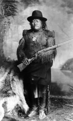 1888? Studio portrait of Chief Nautzille (Nallti Zilli), Mescalero Apache man wearing a buckskin leggings and shirt with epaulets and fringe, moccasins, and a domed felt hat; he holds a rifle.