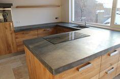 Groot betonnen blad met eiken houten fronten op Ikea kasten met heeeeeeel veel laden. Blad is ter plaatse gemaakt zodat er geen naden ontstaan. Een een plank onzichtbaar bevestigd aan de muur.