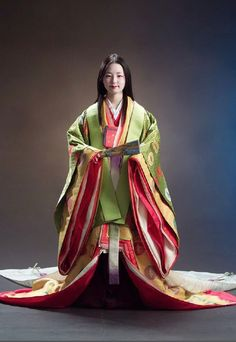 A woman of the Emperor's court.  She is dressed in junihitoe, the traditional twelve layers of kimono in colors appropriate to the season.  Her hair is loose and flowing, and she wears the white makeup demanded by both court protocol and Heian fashion.  Her teeth are most likely blackened, as was also the custom.