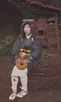 Oharame, or woman from the village of Ohara near Kyoto, seated on bundle of firewood.  About 1930's, Japan