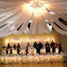 Hang icicle lights under tables and then drape them with sheer fabric. IT will light up your head table and more. #WeddingLights #IcicleLights #HeadTables