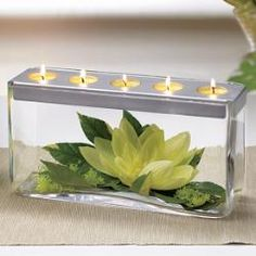 "Customizable Tealight Centerpiece - A silver colored textured finish tray sits elegantly atop hand blown glass displaying treasures like seashells, flowers, or colored marbles. Arrange the contents of this beautiful centerpiece to match your home's décor or change it seasonally. 6""h, 11 3⁄4""w"