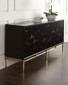 Buffet showcases migrating birds that are reverse painted on black glass. Handcrafted of acacia wood, wood composite, iron, and black glass. Hand painted. Four doors and two adjustable shelves. Doors