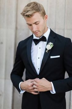 Los angeles glamorous wedding shoot at the culver hotel groom black notch lapel tuxedo with white dress shirt and black bow tie with white pocket square and white floral boutonniere buttoning jacket Black Suit Bow Tie, Black And White Tuxedo, Black Suit Groom, Tuxedo Bow Tie, Tuxedo Suit, Groomsmen Attire Black, Black Tuxedo Wedding, Mens Black Wedding Suits, Groom Tuxedo