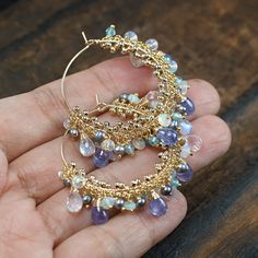 Im back to making more hoop style earrings. :)  Wintry hue gemstones combination of violet Tanzanite, Rainbow Moonstone, AAA Ethiopian Opals, Blue Zircon and Peacock Grey Pearls make up the cluster at the bottom of the hoops. SO dreamy!! The Ethiopian Opals are super flashy and display lovely Green , Blue ,Red , Orange play of colours. The Rainbow Moonstone drops are pure love, these are semi translucent quality and each has beautiful flash on them. I have also weaved tiny 14k gold filled…