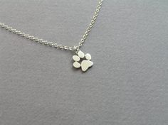 A cute necklace for cats and dogs lovers.  A paw print pendant, handcrafted from sterling silver, with shiny finish. The pendant size is about 0.9 by 0.9 cm/ 0.35 by 0.35 inch. The chain is 45 cm/ 18 inch long. If you want it in a different length, please let me know.  I also make this necklace in 14k (solid) gold: https://www.etsy.com/listing/196711204/paw-print-necklace-pendant-14k-gold?ref=shop_home_active_1  For paw print earrings here…