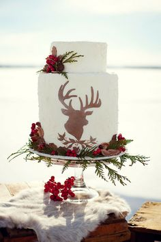 A two-tier winter wedding cake with a fondant deer | Brides.com