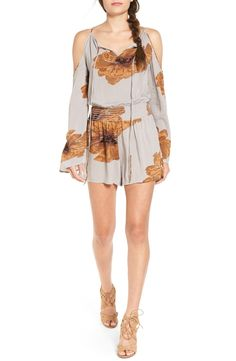 So on trend for summer! Oversized ochre blooms stretch across this flirty romper featuring a shoulder-baring split neckline that cinches with a drawstring tie for a laid-back, boho vibe.