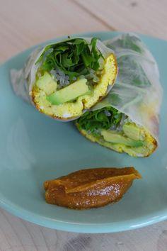 Bereiden:Maak de rice rolls:Kluts de eitjes samen met de kokosroom. Smelt een lepeltje kokosolie in een pannetje en giet het eiermengsel hier in. Bak er een omeltje van. Dompel de rijstvellen in lauwwarm water en leg ze op een snijplank. Beleg de velletjes met een stukje omelet, enkele plakjes avocado, enkele kelp noodles, rucola en druppel er wat sojasaus over. Rol op tot kleine rolletjes en snijd doormidden.Maak de dipsaus:Meng alle ingrediënten voor de dipsaus onder elkaar...