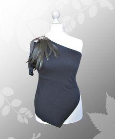Das asymmetrische schwarze One-Shoulder-Top zeigt viel Haut.  Auf der Ärmel-Seite ist eine üppige Appikation aus echten Hahnenfedern, die mit einer Sc