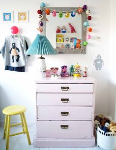 adore this little corner in a lucky child's room with a vintage dresser and colorful garland.  #estella #kids #decor
