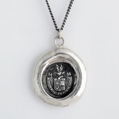 """This handcrafted talisman necklace reads Ni Regret Du Passe Ni Peur De L'Avenir in French, meaning Neither Regret The Past Nor Fear The Future. This seal is a reminder of the happiness that is available to us if we live in the present moment.    Each Pyrrha talisman is cast in reclaimed sterling silver or bronze from a 19th century wax seal and is handcrafted in Vancouver, Canada.    Approx. 3/4"""" x 7/8""""."""