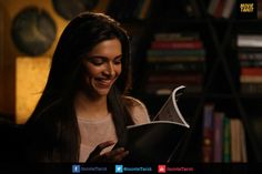 Photo of Deepika Padukone smiling while reading a book in Yeh Jawani Hai Deewani