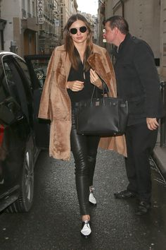 Miranda Kerr: Miranda Kerr dressed up an all-black outfit with surprisingly cool elements — black-and-white oxfords, retro round sunglasses, and a luxe fur coat.