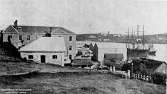 View of the Government Stores and Queens Wharf Road from a vacant block of land, around 1870. Two sailing ships are moored in the Brisbane River, on the right.