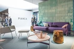 Pianca selects colours contrast to display its new collection at Milan furniture fair. GLIFIi, the selected wallpaper, features blue-aqua green shades of colour to show off the aubergine and bronze tone coloured furnishing accessories.