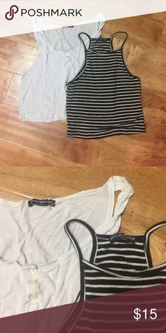 2 Brandy Melville Tops The first one is a black and white striped halter tank crop top in excellent condition. The second is a cropped tank that is an ivory color with buttons, in good condition(showing a little bit of wear). Brandy Melville Tops Crop Tops