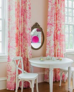 Pretty pink girl's bedroom features an antique oval shaped mirror atop baby pink walls framing windows dressed in cream and pink toile drapes with a round white play table in front lined with white bistro chairs.
