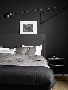 I'm loving this dark bedroom with the Serge Mouille look-a-like wall lamp and stone-gray linen on the bed - via Anna Gillar
