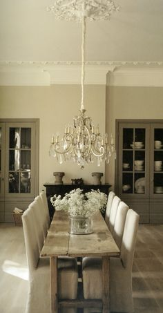 Slipcovered chairs pair with rustic table and glam chandelier. dark grey cabinets set it off
