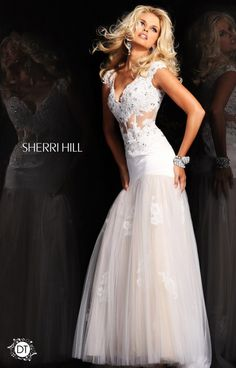 Sherri Hill 21012 is just plain sexy! Looking for a sheer dress with gorgeous lace details? Hello! Here it is! The cap sleeves are slightly sheer, matching the waist that is totally showing lots of skin. The fitted top leads into a drop waist skirt that flares out at the lower hip into an almost mermaid style skirt.