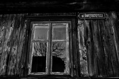 A bare winter tree is reflected in the window of an old wooden house in Pabianice, Poland.