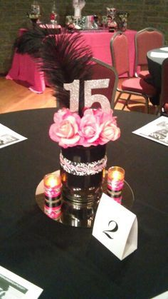 Pink and black Paris Quinceanera centerpiece...spray painted large glass vase, damask ribbon...added flowers and feathers